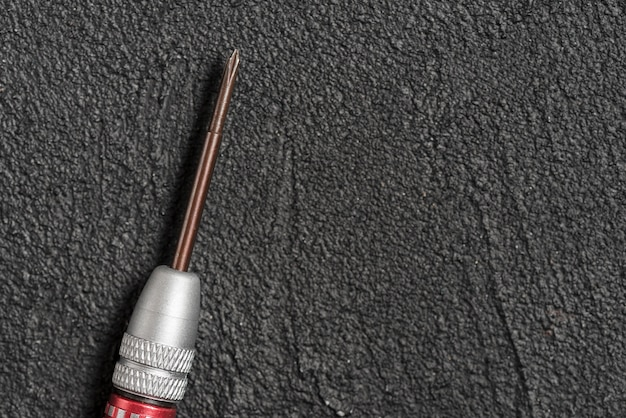 High angle view of screwdriver on rough black background