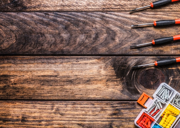 High angle view of screwdrivers and bolt kit on wooden background