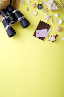 High angle view of seashells by binoculars and jewelry over yellow