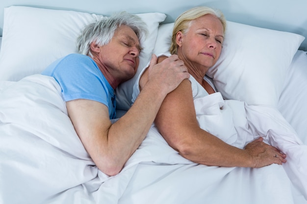 High angle view of senior couple sleeping on bed