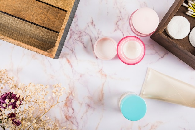 High angle view of skin care creams on marble