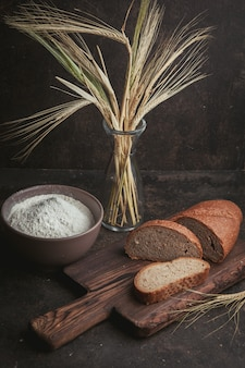 High angle view slice of bread with flour in a bowl and wheat on cutting board and dark brown.