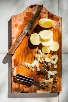 High angle view of sliced potatoes with knife on wooden cutting board