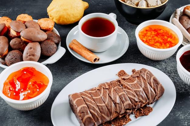 暗闇の中で紅茶、小さなケーキ、ワッフル、ゼリーのプレートでルラードをスライスした高角度のビュー