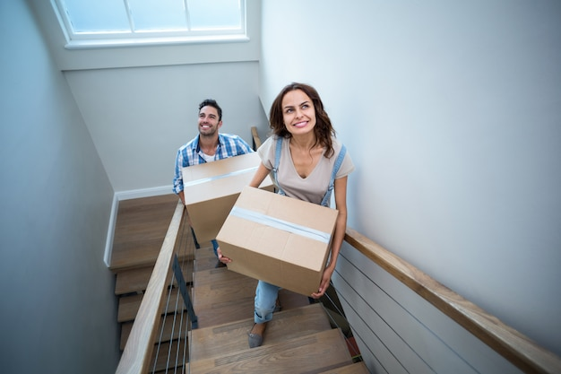 High angle view of smiling couple holding cardboard boxes while climbing steps