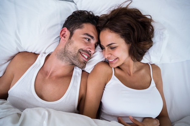 High angle view of smiling couple relaxing on bed