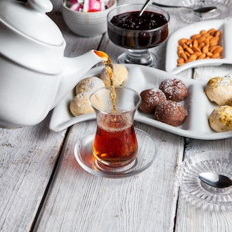 High angle view someone pouring tea with desserts, nuts, fruit jam on white wooden background.