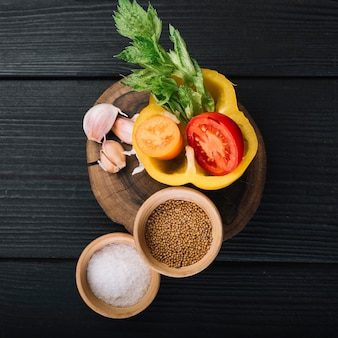 High angle view of spices and ingredients on black wooden surface