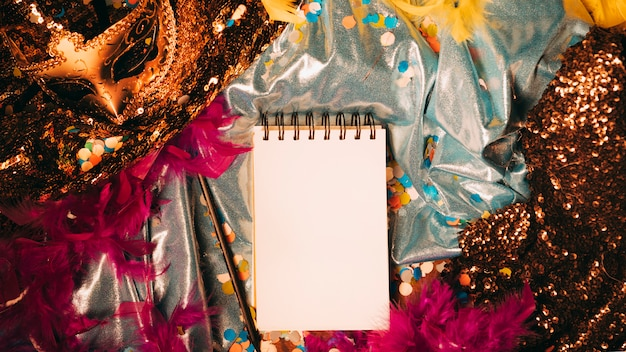 High angle view of spiral blank notepad with carnival props