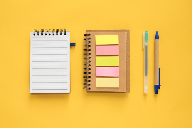 High angle view of spiral notepad; adhesive notes and pen on yellow background