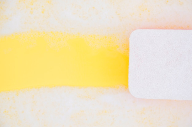High angle view of sponge cleaning soap sud on yellow backdrop