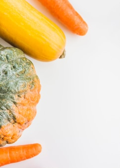 High angle view of squash and carrots on white surface