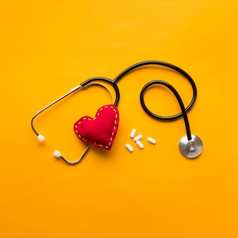 High angle view of stethoscope; stitched heart and medicines over yellow backdrop