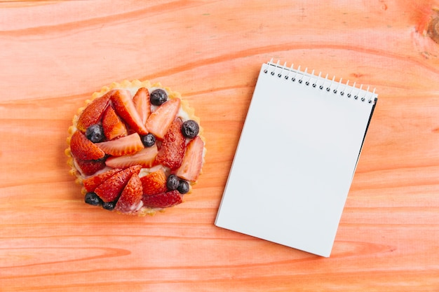 High angle view of strawberry tart and spiral notepad on wooden surface