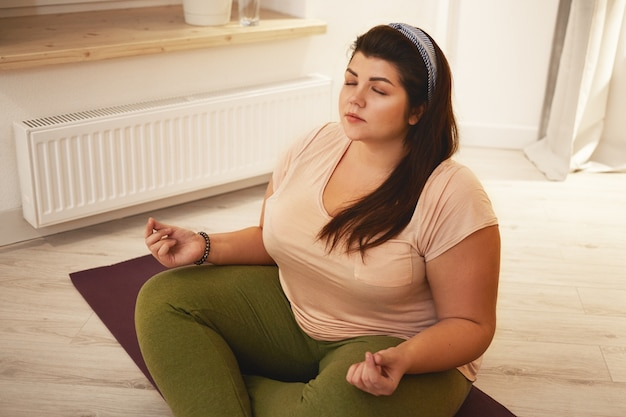 High angle view of stylish young chubby overweight woman dressed in leggings and t-shirt meditating with legs crossed, closing eyes, holding hands in mudra, practicing breathing techniques