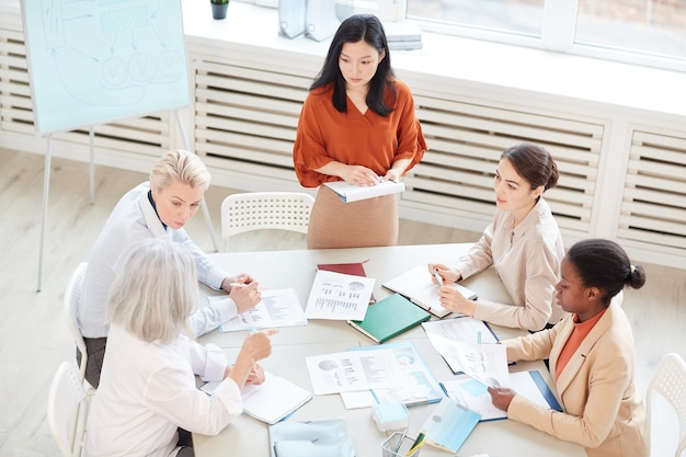 High angle view at successful asian businesswoman presenting project plan to group of female colleagues while standing by whiteboard during meeting in conference room