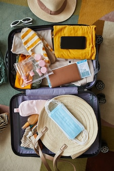 High angle view of suitcase with clothes airplane tickets and masks in it packing in vacation