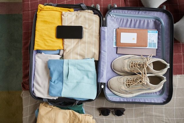 High angle view of suitcase with clothes shoes and passport with tickets packing for journey