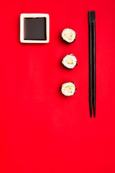 High angle view of sushi rolls with chopsticks and soya sauce over red background