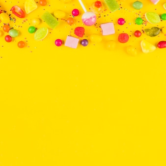 High angle view of sweet candies on yellow background