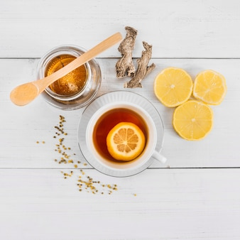 High angle view of sweet honey; lemon tea and ginger on wooden background