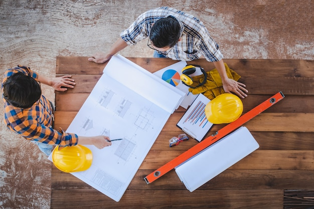 High-angle view of a team of construction engineers and two architects at the meeting to design the construction and discuss house drafting and building planning in the construction area.