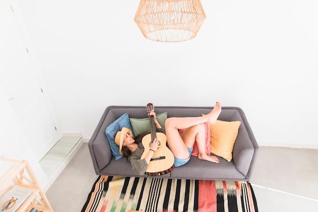 High angle view of a teenage girl lying on sofa playing guitar