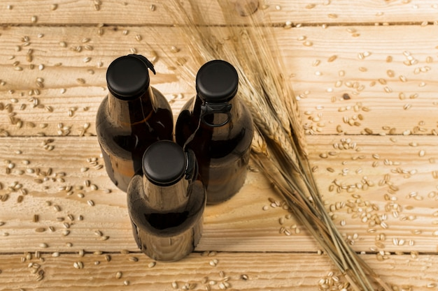 High angle view of three alcoholic bottles and ears of wheat on wooden surface
