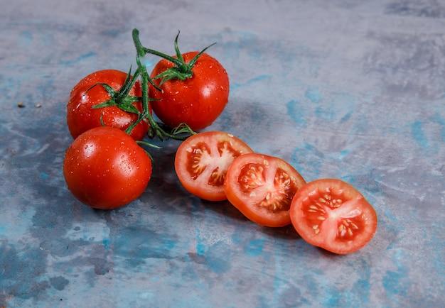 Pomodori di vista dell'angolo alto con le fette su superficie strutturata. orizzontale