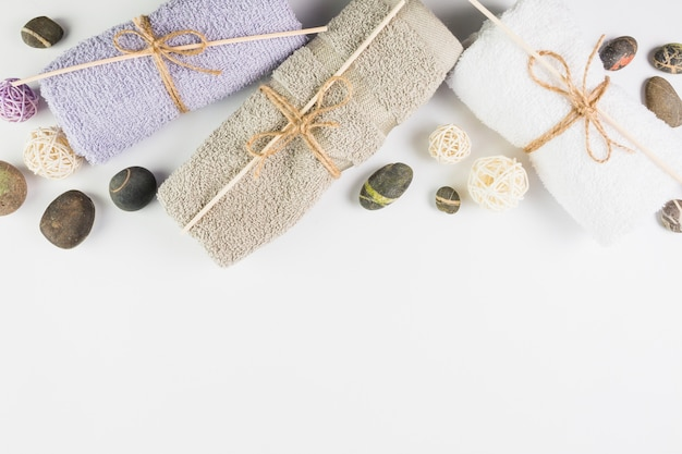High angle view of towels and spa stones on white backdrop