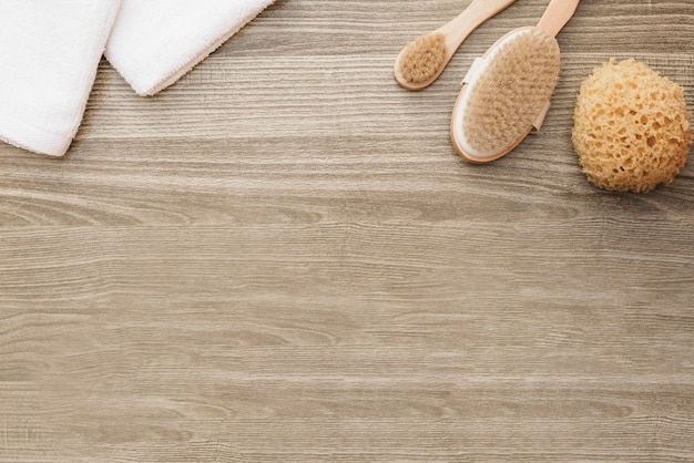 High angle view of towels; sponge and brush on wooden background