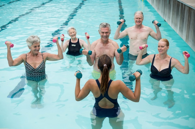 High angle view of trainer and senior swimmers exercising in swimming pool
