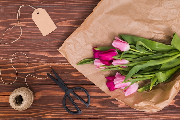 High angle view of tulip flowers; brown paper; price tag; string and scissor over wooden backdrop