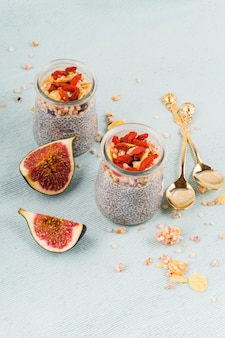 High angle view of two jar chia seeds pudding; golden colored spoon and fig slices on colored background