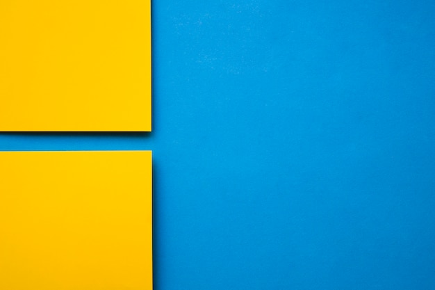 Un punto di vista dell'angolo alto di due carte gialle del cartone su fondo blu