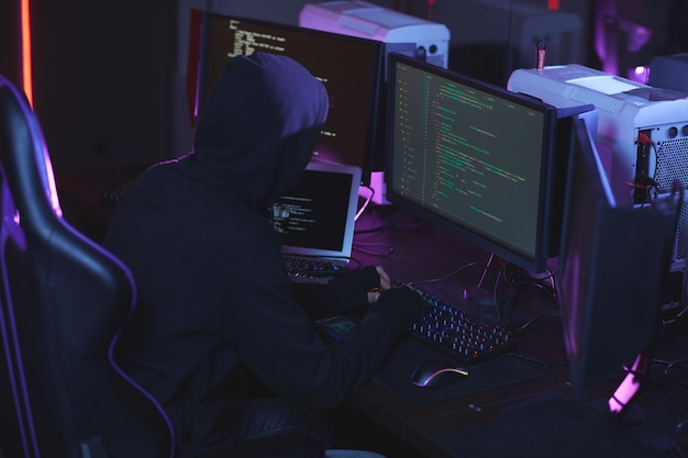 High angle view at unrecognizable cyber security hacker wearing hood while working on programming code in dark room, copy space
