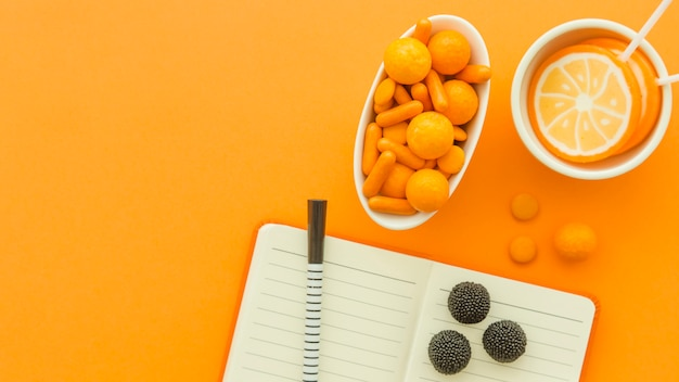 High angle view of various candies and lollipops with notepad and pen on orange surface