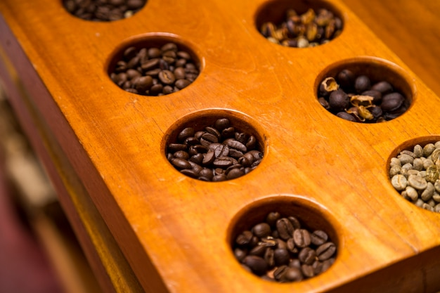High angle view of various coffee beans in wooden container