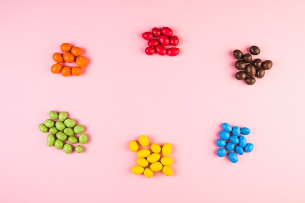 High angle view of various colorful candies on pink background