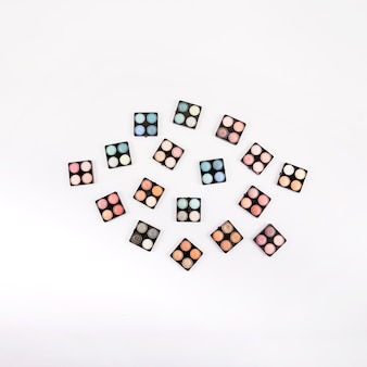 High angle view of various eye shadow powders on white background