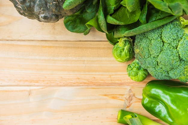 High angle view of various fresh green vegetables on wooden background