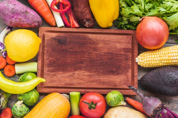 High angle view of various fresh vegetables surrounding chopping board