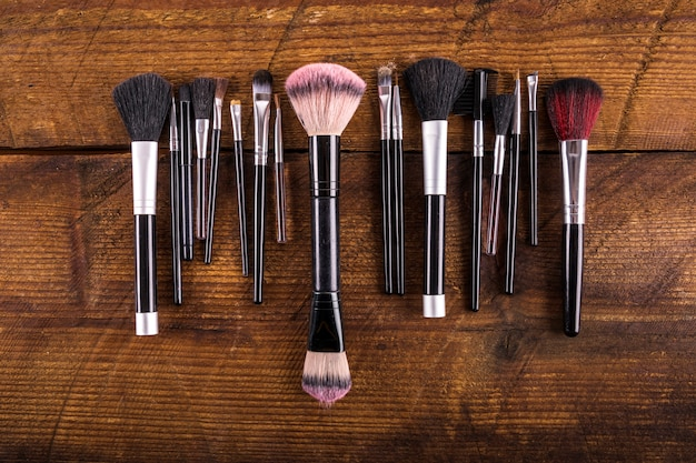 High angle view of various makeup brushes on wooden backdrop