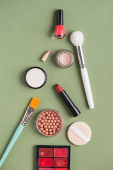 High angle view of various makeup products on green background