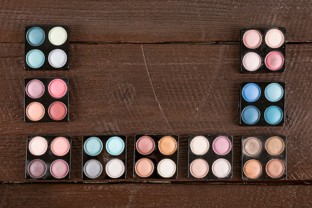 High angle view of a various multi colored eyeshadow powder on wooden background