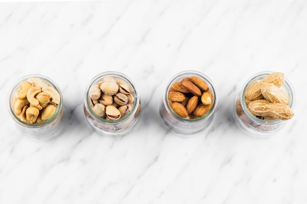 High angle view of various nut food jar on marble background