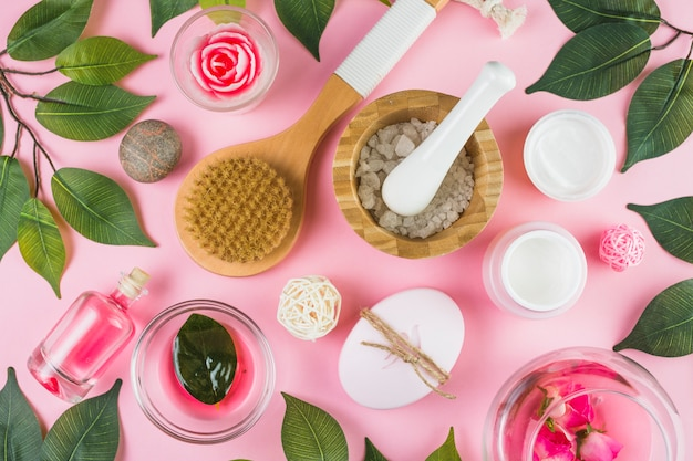 High angle view of various spa products and green leaves on pink background