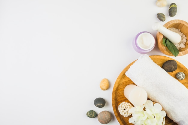 High angle view of various spa products on white backdrop
