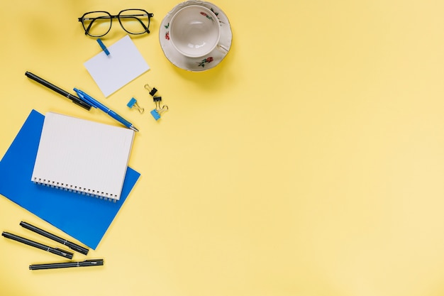 High angle view of various stationeries and cup on yellow background