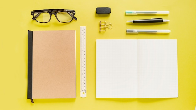 High angle view of various stationeries on yellow backdrop